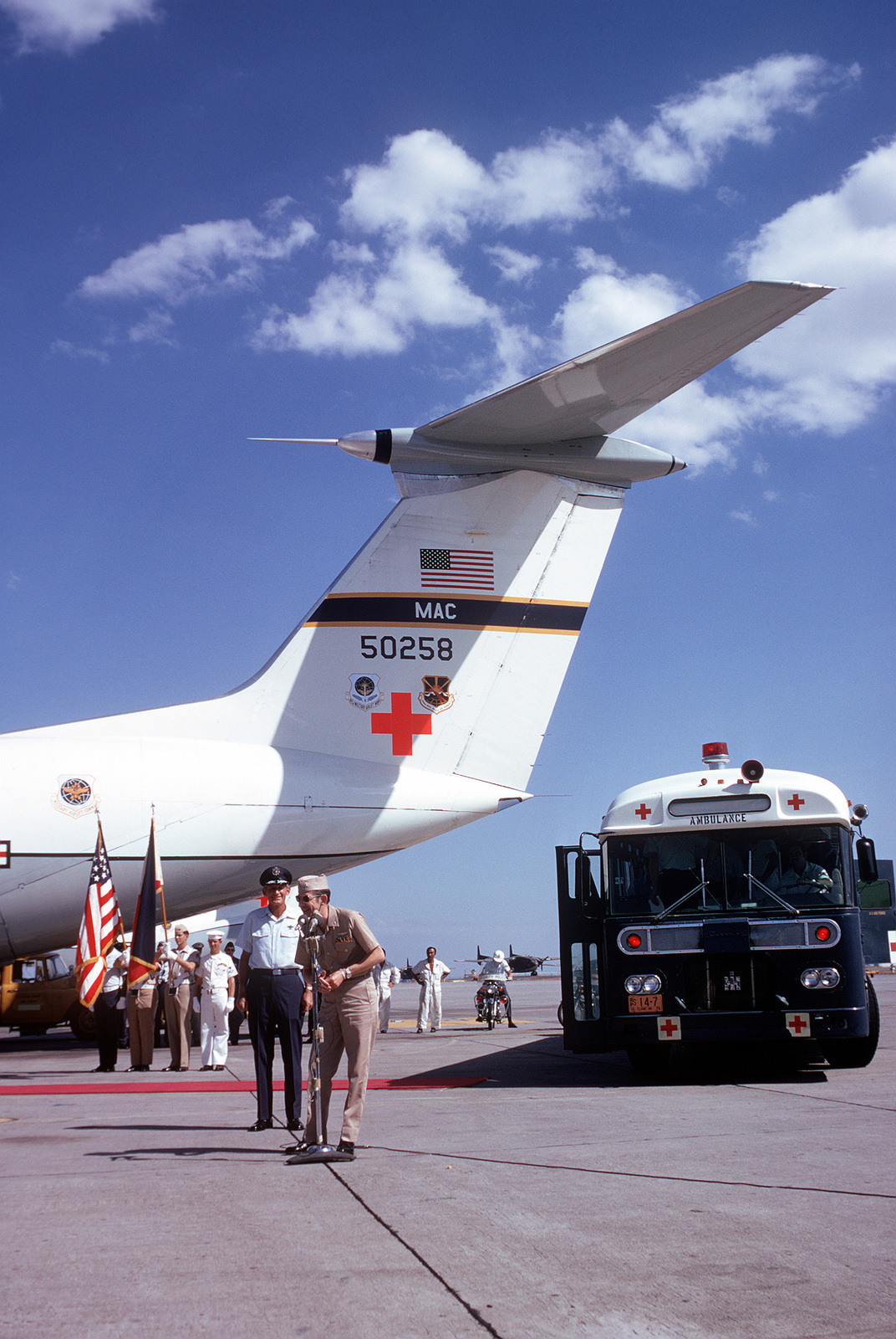 Ex-POW and U.S.Navy CMDR James Glenn Pirie (Captured 22 Jun 67), at the flight line microphone, thanks the crowd of well wishers and press before departing for the United States on the C-141 Starlifter in the background. 13th Air Force Commander, LGEN William G. Moore Jr., stands in background near the ambulance bus that brought the ex-POWs to the flight line. CMDR Pirie was released in Hanoi by North Vietnam on 18 Feb 73