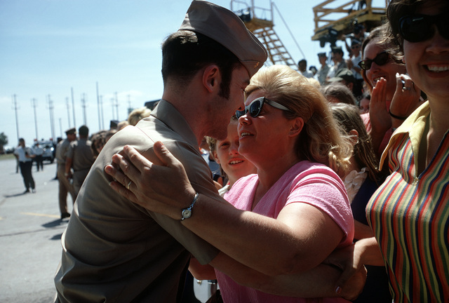 An unidentified Navy ex-POW gets a hug from one of the many well wishers who came to the flight line to say goodbye as he leaves for United States