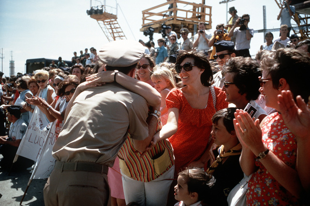 Ex-POW and U.S. Navy CMDR Collins Henry Haines (Captured 5 Jun 67) gets farewell hug from one of the many well wishers who came to the flight line to say goodbye as he leaves for the United States. CMDR Haines was released in Hanoi by North Vietnam on 4 Mar 73