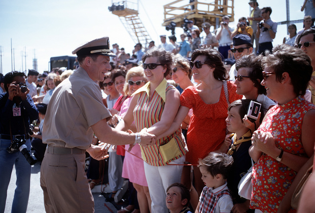 Ex-POW and U.S. Navy CMDR Collins Henry Haines (Captured 5 Jun 67) shakes hands with some of the many well wishers who came to the flight line to say goodbye as he leaves for the United States. CMDR Haines was released in Hanoi by North Vietnam on 4 Mar 73