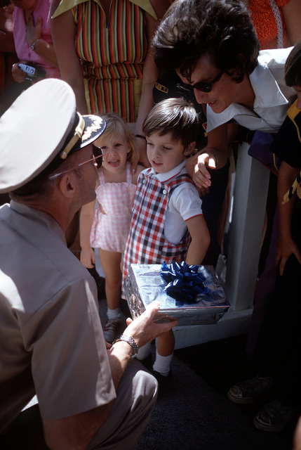 Ex-POW and U.S. Navy CPT Ernest Milvin Moore Jr., (Captured 11 Mar 67) gets a gift from young Robert Ballentine, son of SSGT Michael G. Ballentine assigned to the 6922nd Security Squadron. He was one of the many well wishers who came to say goodbye to CPT Moore as he leaves for United States. CPT Moore was released in Hanoi by North Vietnam on 4 Mar 73