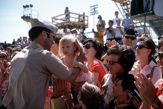 Unidentified ex-POW, U.S. Navy LT holds a small girl as he says farewell to a crowd of well wishers who came to the flight line to say goodbye as he leaves for the United States