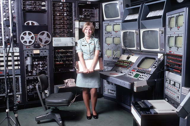 A female U.S. Army audiovisual technician stands beside a videotape editing console