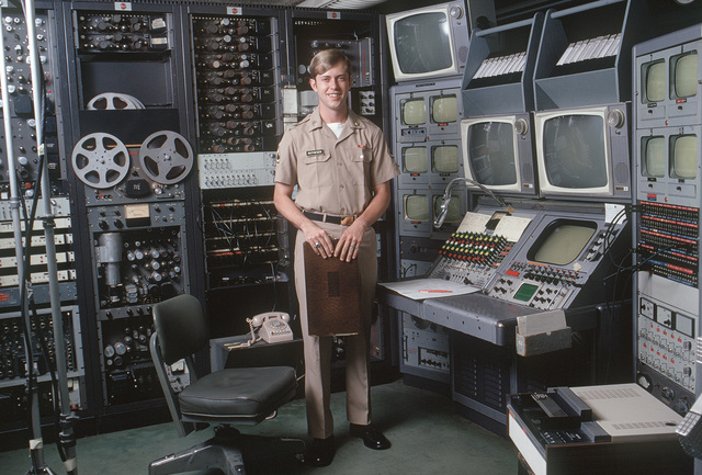 A US Army audiovisual technician stands beside a videotape editing console