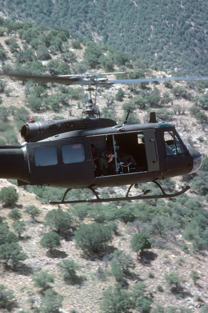 A US Army photographer takes photographs from a UH-1 Iroquois helicopter in flight