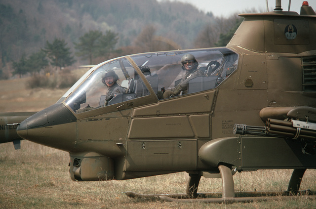 A US Army pilot and copilot stand by for take off in an AH-1G Cobra helicopter