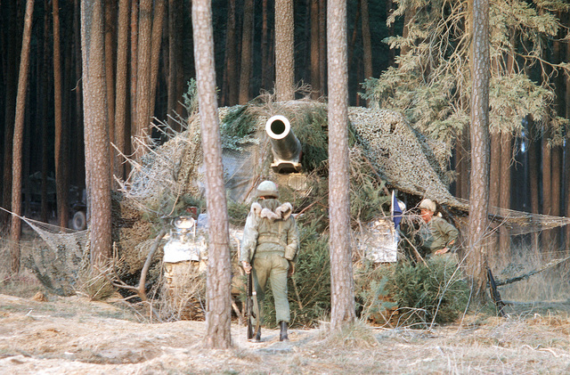 Artillerymen camouflage an M-110 203mm (8-inch) self-propelled howitzer during a field training exercise