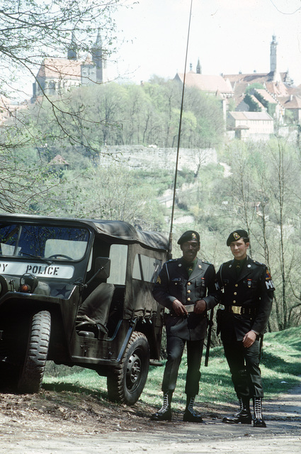 US Army military policemen on duty in a European town. Their M151 light vehicle is nearby