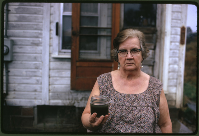 Mary Workman Holds a Jar of Undrinkable Water that Comes from Her Well, and has Filed a Damage Suit against the Hanna Coal Company, She has to Transport Water from a Well Many Miles Away Although the Coal Company Owns All the Land around Her, and Many Roads Are Closed, She Refuses to Sell