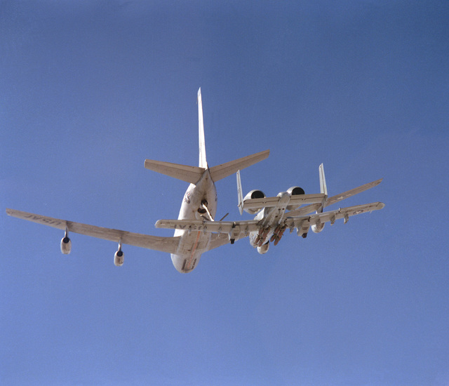 An air-to-air rear view of a YA-10 aircraft being refueled by a KC-135 Stratotanker