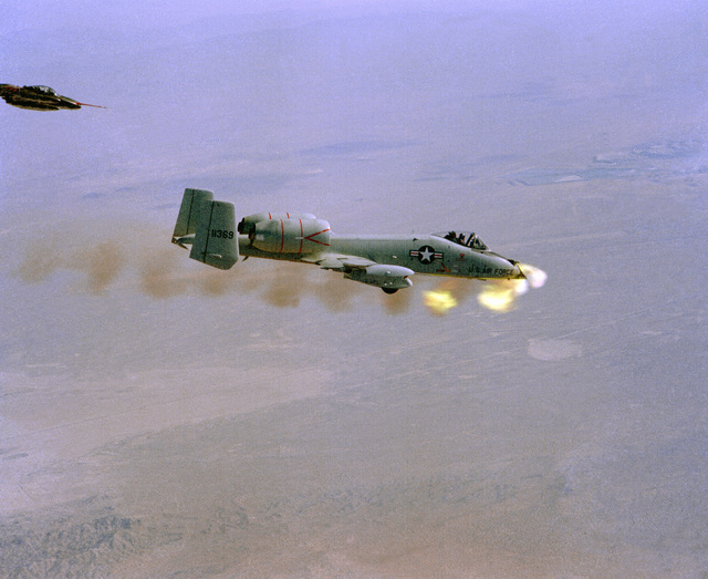 An air-to-air right side view of a YA-10 aircraft firing its GAU-8 30mm gun during a test