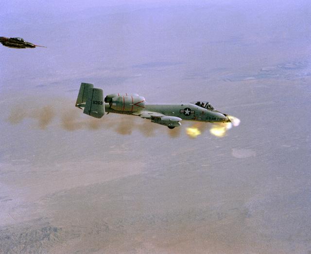 An air-to-air right side view of a YA-10 aircraft firing its GAU-8 30mm gun during a test