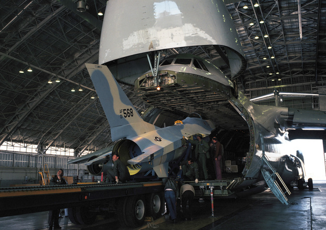 A YF-16 aircraft is offloaded from a C-5A Galaxy aircraft in a hangar