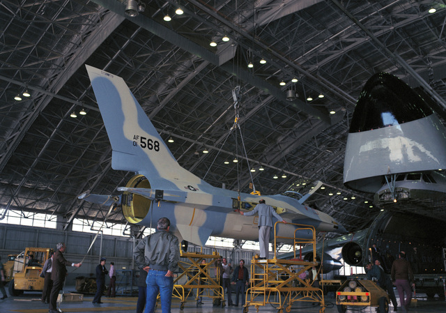 A YF-16 aircraft is offloaded from a C-5A Galaxy aircraft inside a hangar