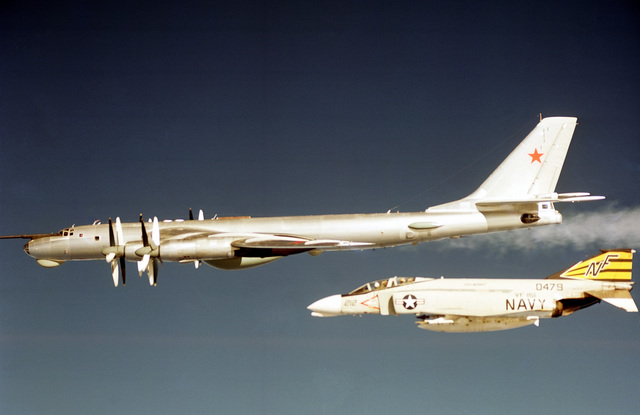 An air-to-air left side view of a Soviet Tu-95 Bear D aircraft as an F-4 Phantom II aircraft from Fighter Squadron 151 (VF-151) intercepts it