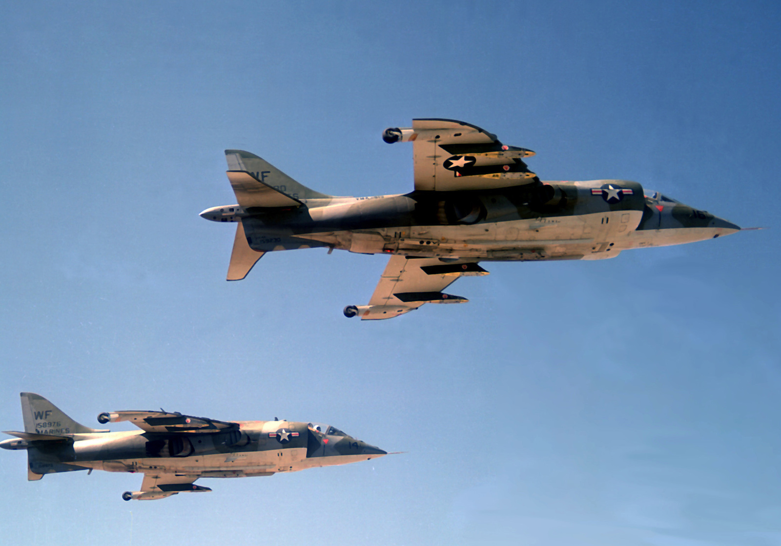 An air-to-air right side view of two Marine Fighter Attack Squadron 513 (VMFA-513) AV-8A Harrier aircraft