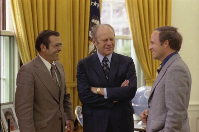 Photograph of President Gerald R. Ford Chatting with Chief of Staff Donald Rumsfeld and Rumsfeld's Assistant Richard Cheney in the Oval Office