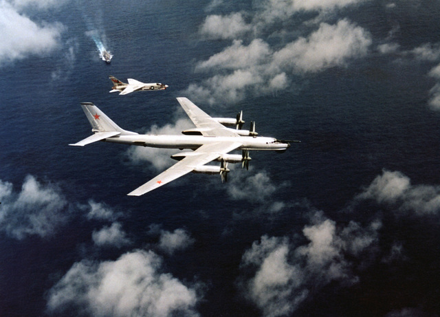 An air-to-air right side view of an F-8 Crusader aircraft as it intercepts a Soviet TU-95 Bear-A/B aircraft near the aircraft carrier USS ORISKANY (CVA-34)