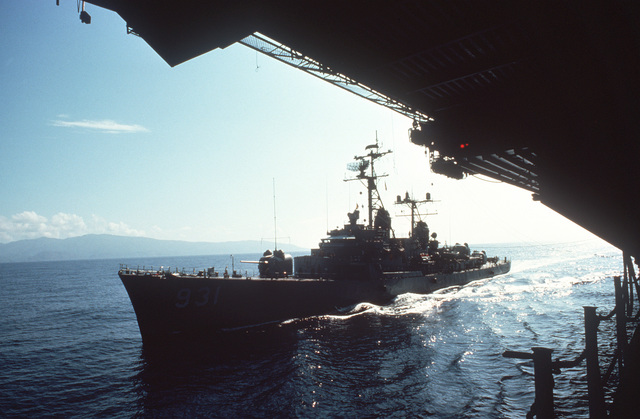 A port bow view of the destroyer USS FORREST SHERMAN (DD-931) alongside an aircraft carrier during an underway replenishment