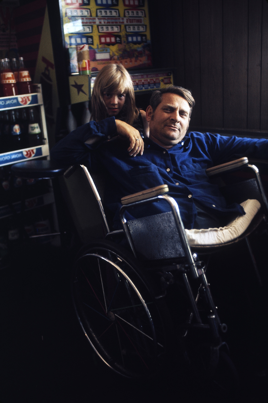 Jack Smith, 42, a Disabled Miner Who Lives in Rhodell, West Virginia, Shown with One of His Daughters, Debra, in the Tavern He Now Operates, He Had Worked in the Mines One Year When His Legs were Crushed in a Roof Cave-in, it Took Him 18 Years to Received Workman's Compensation, His Wheelchair was Bought for Him by His Friend, Arnold Miller, Now President of the United Mine Workers Smith is Active in the Union, and Has Manned Picket Lines in the Past