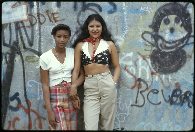 Two Latin Girls Pose in front of a Wall of Graffiti in Lynch Park in Brooklyn, New York City, this Project is a Portrait of the Inner City Environment, it Contains Life, Great Murals on the Walls of Buildings and People Enjoying Themselves, Today's Inner City is a Contradiction to Main Stream America's Gas Stations Expressways Shopping Centers and Tract Homes, Blacks, Latins, and Poor Whites Live There