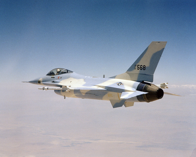 An air to air left side view of a YF-16 Fighting Falcon aircraft armed with AIM-9 Sidewinder missiles on the wing tips