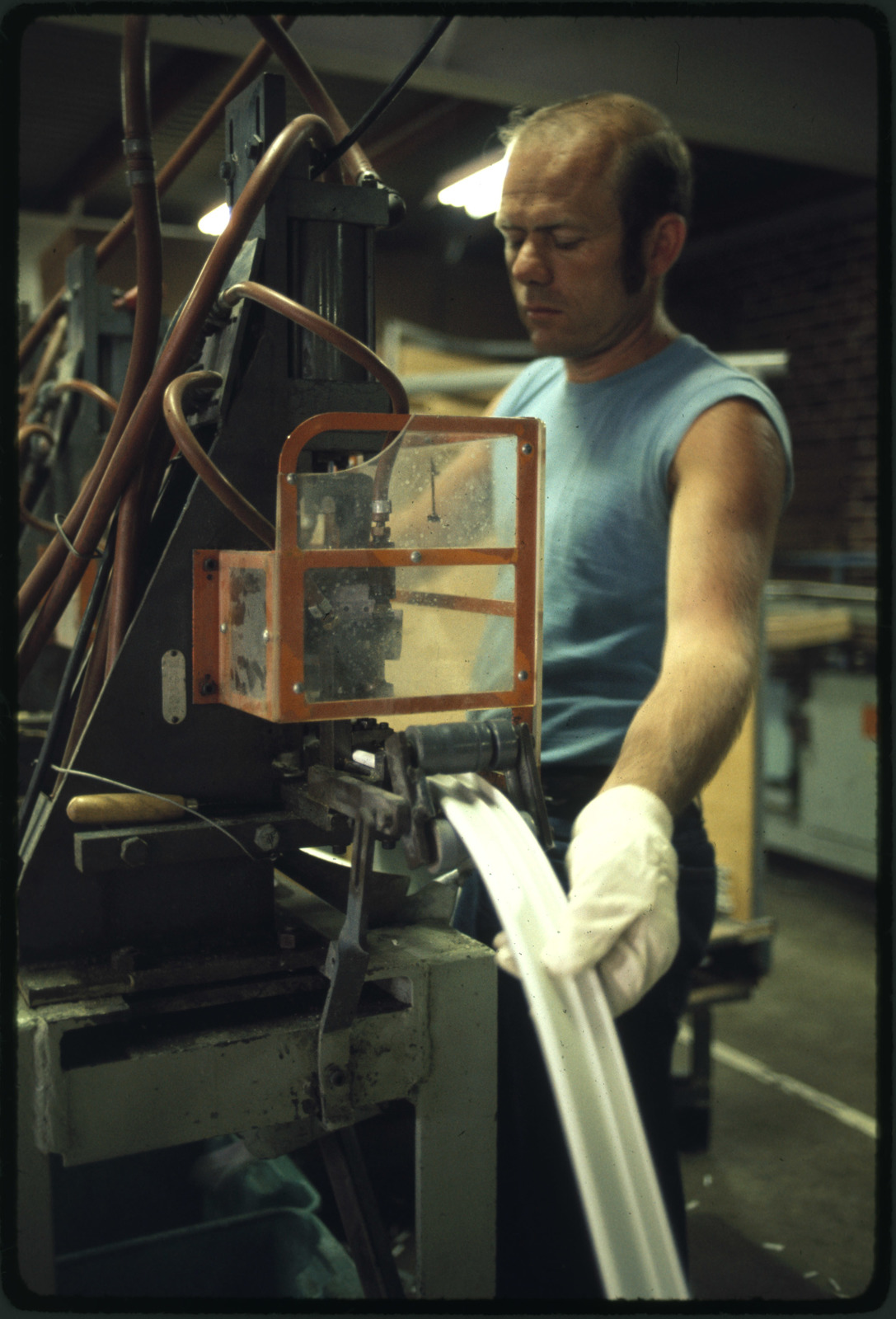 Employee of the B. F. Goodrich Co. Working on a Machine That Makes Molding for Magnetic Doors Seals for Various Brands of Refrigerators, the Firm Employs 184 People which Makes it the Third Largest Employer in Town Behind the 3m Co.(Minnesota Mining and Manufacturing) with 1,377 and Kraft Foods with 487, New Ulm is a Country Seat of 13,000 in a Farming Area of South Central Minnesota Founded in 1854 by a German Immigrant Land Company