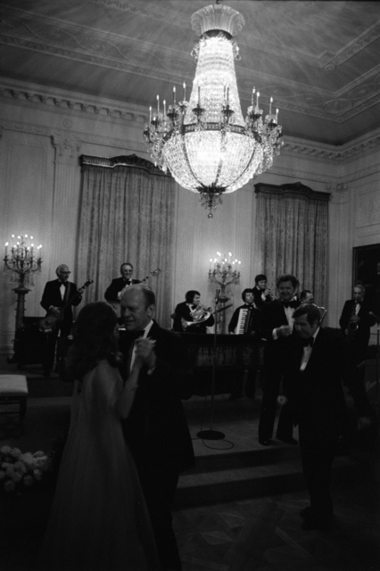 Photograph of President Gerald R. Ford Dancing with Queen Alia of Jordan in the East Room while the Howard Devron Orchestra Plays during a State Dinner Held in Honor of the King of Jordan