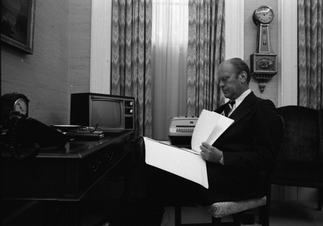 Photograph of President Gerald R. Ford Reviewing the Text of his Pardon Message in Adviser Robert Hartmann's Office before Publicly Announcing his Decision to Pardon Former President Richard Nixon