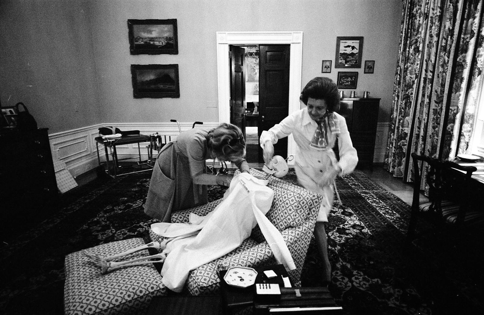 First Lady Betty Ford and Her Secretary Nancy Howe Dressing a Skeleton for Halloween in the President's Chair in His Private Study on the Second Floor of the White House