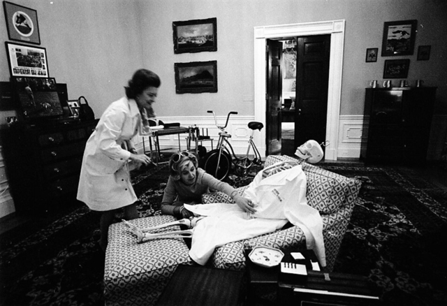 Photograph of First Lady Betty Ford and Her Secretary Nancy Howe Dressing a Skeleton for Halloween in the President's Chair in His Private Study on the Second Floor of the White House