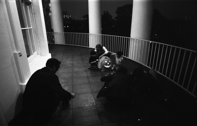 Photograph of Susan Ford and Unidentified Children Carving a Halloween Pumpkin on the Truman Balcony While the Press Takes Photos