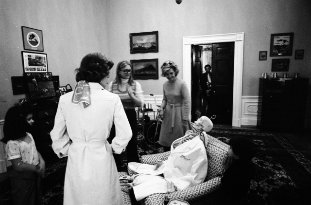 Susan Ford and an Unidentified Child Look At a Skeleton First Lady Betty Ford and her Secretary Nancy Howe Dressed for Halloween in the President's Private Study on the Second Floor of the White House