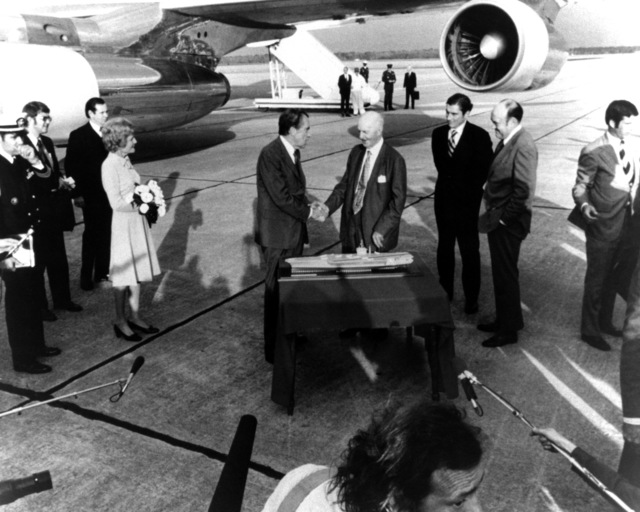 President Richard Nixon,  left, shakes hands with former congressman (D-Ga.) Carl Vinson with a model of the nuclear-propelled aircraft carrier slated to be named after the congressman.  Standing to the right are Secretary of the Navy John Warner, dark suit, and Secretary of Defense Melvin Laird