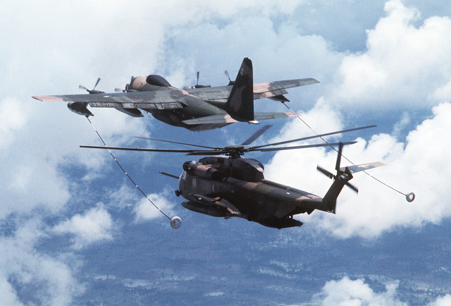 A view of an in-flight HC-130P Hercules aircraft maneuvering to refuel an HH-53 Super Jolly helicopter