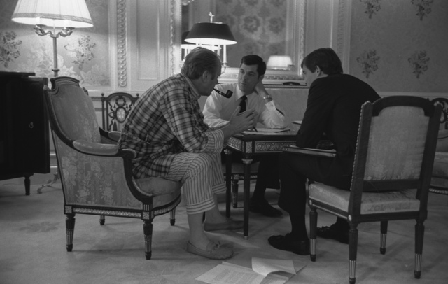 Photograph of President Gerald R. Ford, in his Pajamas,Meeting with Staff Members Steve Todd (Military Aide) and Terry O'Donnell in the President's Suite in the Akasaka Palace, Tokyo, Japan