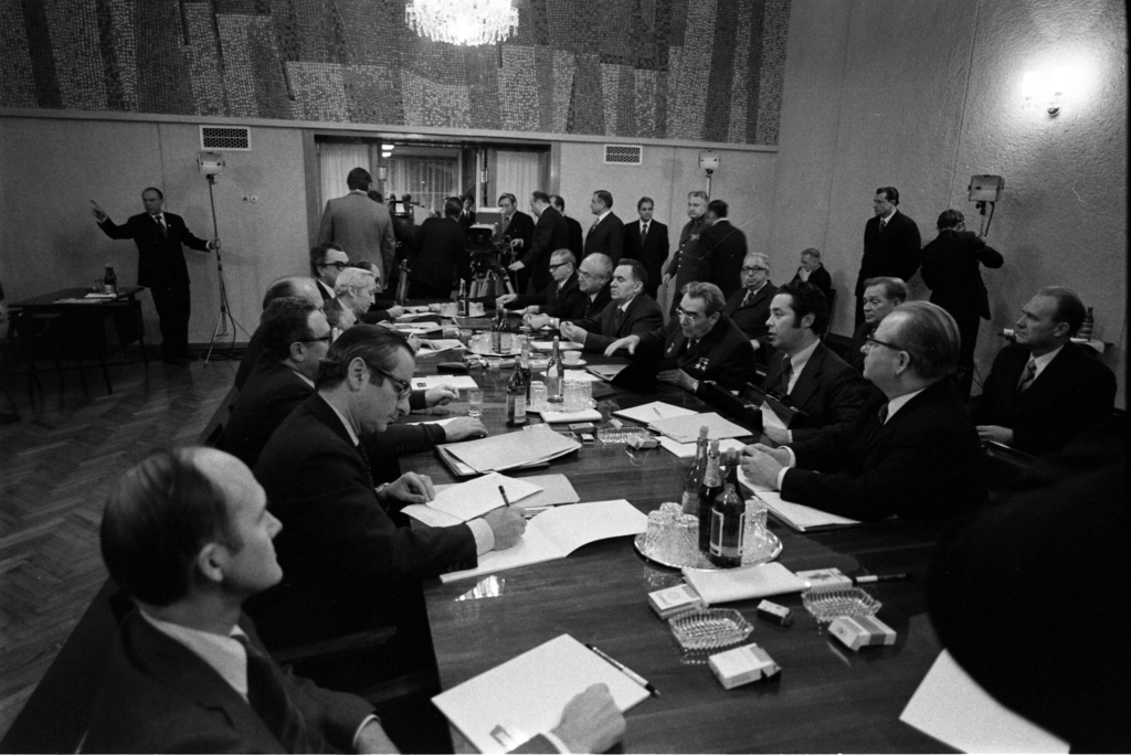 Photograph of the First Meeting between President Gerald Ford, Soviet General Secretary Leonid Brezhnev, and the Delegations in the Conference Hall at Okeansky Sanatorium, Vladivostok, U.S.S.R.