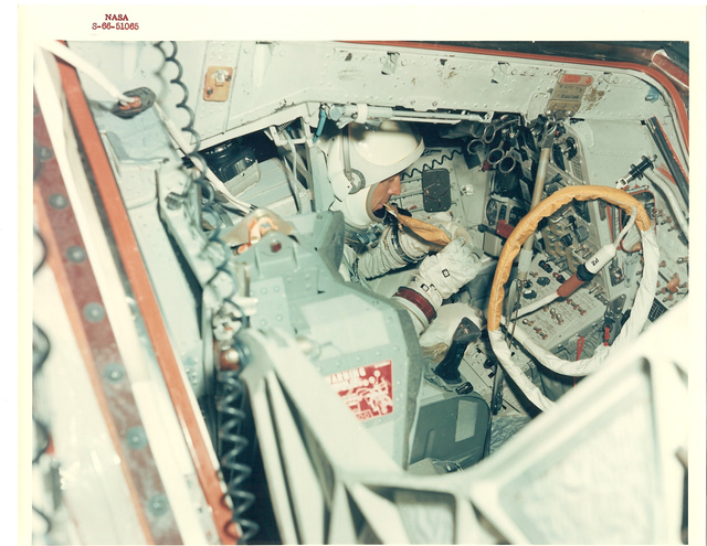 Photograph of Astronaut Cooper inside 30' Altitude Chamber and Using Food Packets