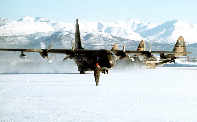 A ground crewman marshals a C-130 Hercules aircraft into a parking position during Exercise Jack Frost '75