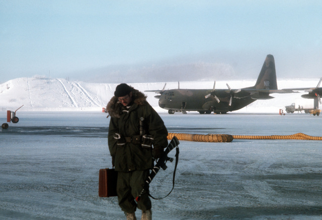 An Army troop member is leaving a C-130 Hercules aircraft after arrival during Exercise Jack Frost '75