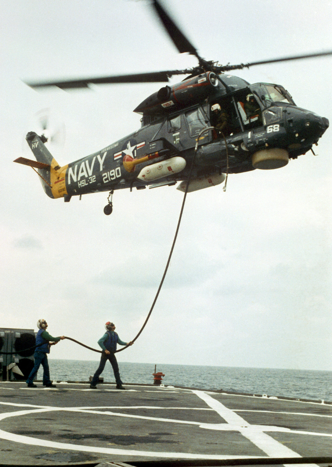 Right side view of an SH-2F Seasprite Mark 1 Light Airborne Multi-Purpose System (LAMPS) helicopter, hovering above the flight deck. The helicopter is from the Light Helicopter Anti-submarine Squadron 32 (HSL-32)