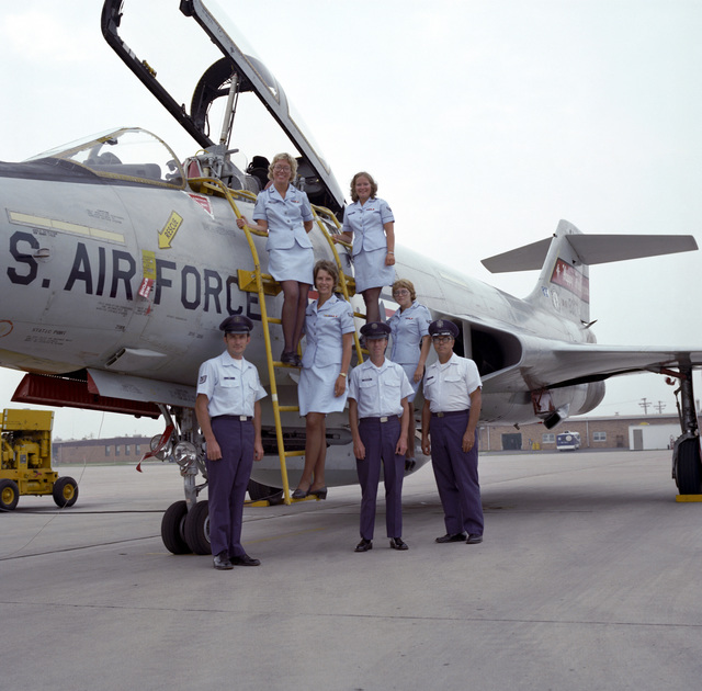 "U.S. Air Force Airmen assigned to the 119th Fighter Wing""Happy Hooligans"", North Dakota Air National Guard, pose for a photo on a F-101B Voodoo aircraft, at Hector International Field, North Dakota. Pictured left-to-right, (top row) SGT. Patricia McMerty, SGT. Ellen Rising, (Middle row) SGT. Doreen Thomas, AIRMAN 1ST Class Jacqueline Sanders, (bottom row), TECH. SGT. Phillip Poe, MASTER SGT. James Schreiner, and LT. COL. Allan Eide. (A3604) (U.S. Air Force PHOTO) (Released)"