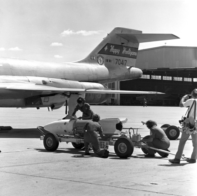 """U.S. Air Force female Weapons Handler SGT. Patricia McMerty, SGT. Ellen Rising, and SGT. Merlin Doorheim, all assigned to the 119th Fighter Wing""""Happy Hooligans"""", North Dakota Air National Guard, practice weapons loading onto a F-101B Voodoo aircraft, at Hector International Field, North Dakota, for the upcoming William Tell""""Weapons Competition to be held at Tyndall, Air Force Base, Florida. (A3604) (U.S. Air Force PHOTO) (Released)"""