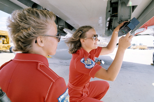 """U.S. Air Force female Weapons Handler SGT. Patricia McMerty, SGT. Ellen Rising, and SGT. Doreen Thomas, part of the first all female weapons load team assigned to the 119th Fighter Wing""""Happy Hooligans"""", North Dakota Air National Guard, practice weapons loading onto a F-101B Voodoo aircraft, at Hector International Field, North Dakota, for the upcoming William Tell""""Weapons Competition to be held at Tyndall, Air Force Base, Florida. (A3604) (U.S. Air Force PHOTO) (Released)"""