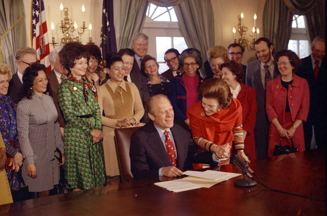 Photograph of First Lady Betty Ford Congratulating President Gerald Ford for Signing an Executive Order Establishing a National Commission for the Observance of International Women's Year 1975
