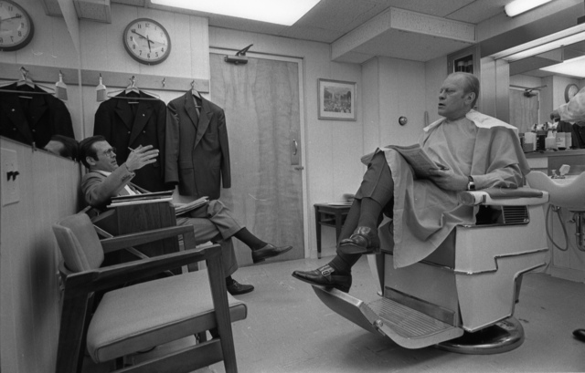 President Gerald R. Ford Talks with Donald Rumsfeld while he is Sitting in a Barber Chair for a Haircut Prior to an Address to the Nation on Energy and Economic Problems