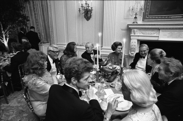 Photograph of First Lady Betty Ford, Prime Minister Harold Wilson of Great Britain, Happy Rockefeller, Cary Grant, Eileen Mehle, Van Cliburn,  Mrs. Winston Guest, Danny Kaye, Margaret Truman Daniel, and British Secretary of State James Callaghan Seated in the State Dining Room  during a State Dinner Honoring Prime Minister Wilson