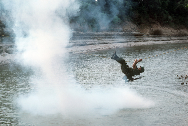 A US Army soldier crosses a river on a rope during a field training exercise