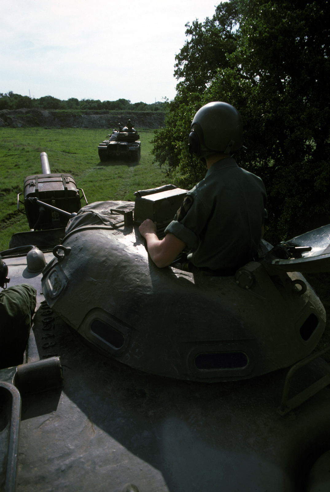 A US Army tank commander looks out from the cupola of his M60 main battle tank during a field training exercise