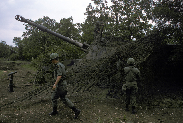 US Army soldiers drape camouflage netting over an M109A1 155 mm self-propelled howitzer during a field training exercise